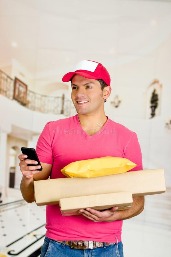 Livreur dans l'uniforme rose tenant des boîtes et des documents photos stock