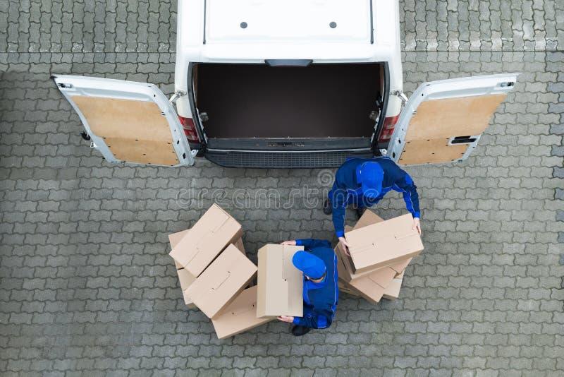 Livreurs déchargeant des boîtes en carton de camion sur la rue photos stock