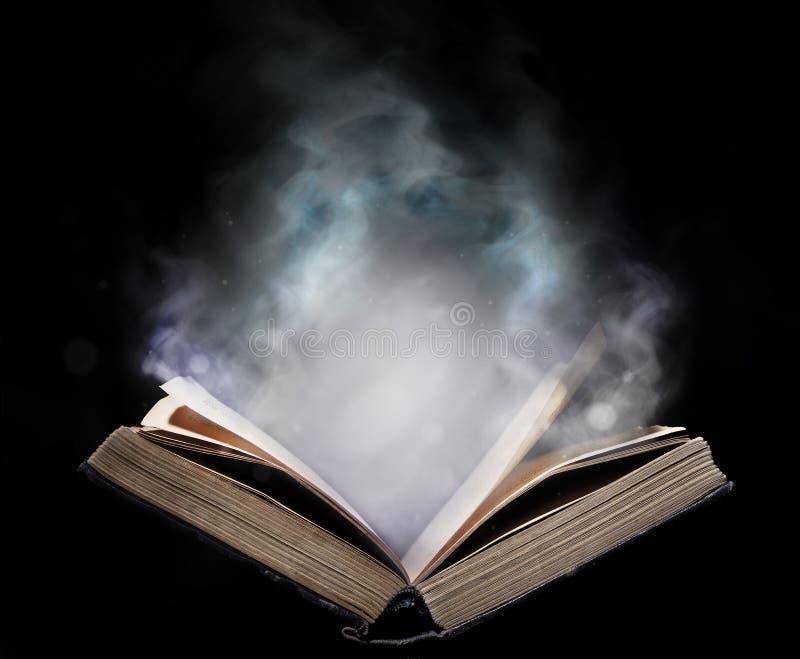 Livro aberto antigo no fumo mágico imagens de stock