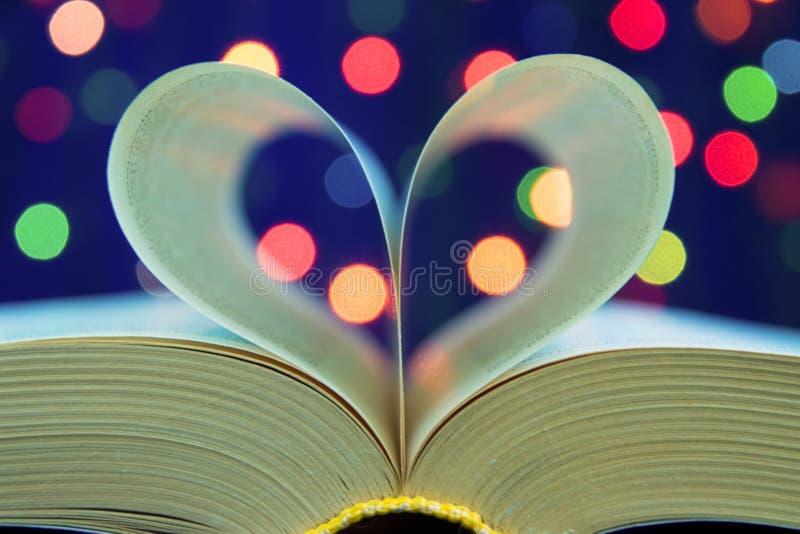 Livro aberto com forma do coração das páginas de papel na tabela no fim macio do estilo do feriado da luz da noite acima com fund fotografia de stock royalty free