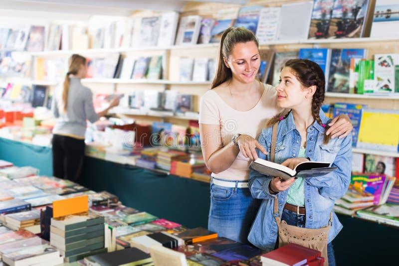Livro aberto da exibição contente da mulher à menina feliz no boutique do livro fotografia de stock royalty free
