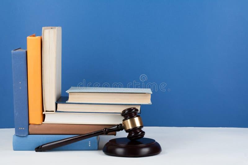 Livro aberto do conceito da lei com o martelo de madeira dos juizes na tabela em uma sala do tribunal ou em um escritório da apli fotos de stock