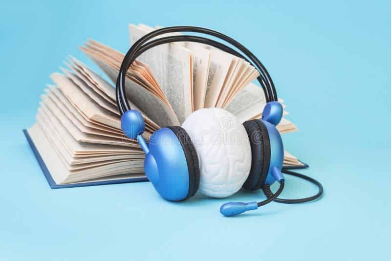 Livro aberto e um cérebro em fones de ouvido azuis fotografia de stock
