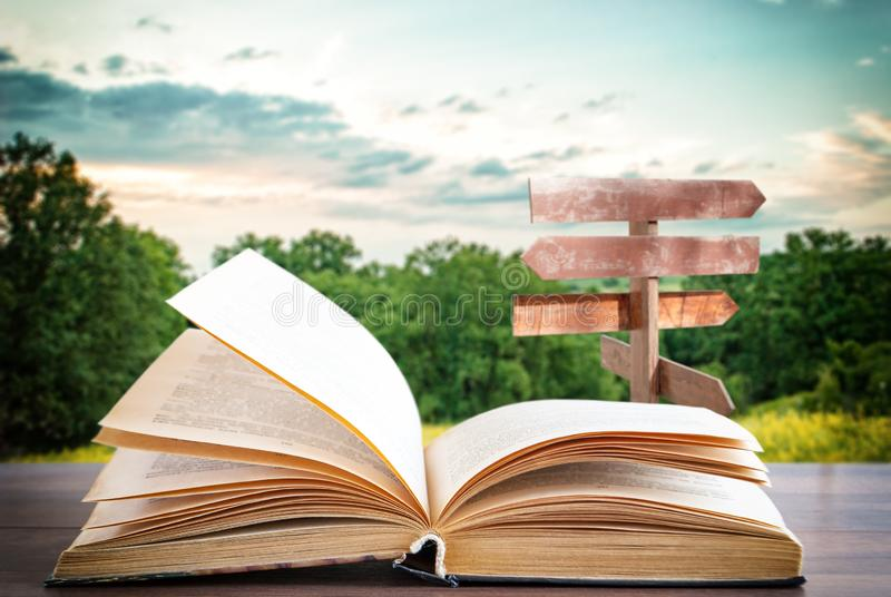 Livro aberto em uma superfície de madeira e um ponteiro no fundo foto de stock