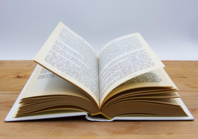 Livro aberto na tabela de madeira, fundo branco imagens de stock