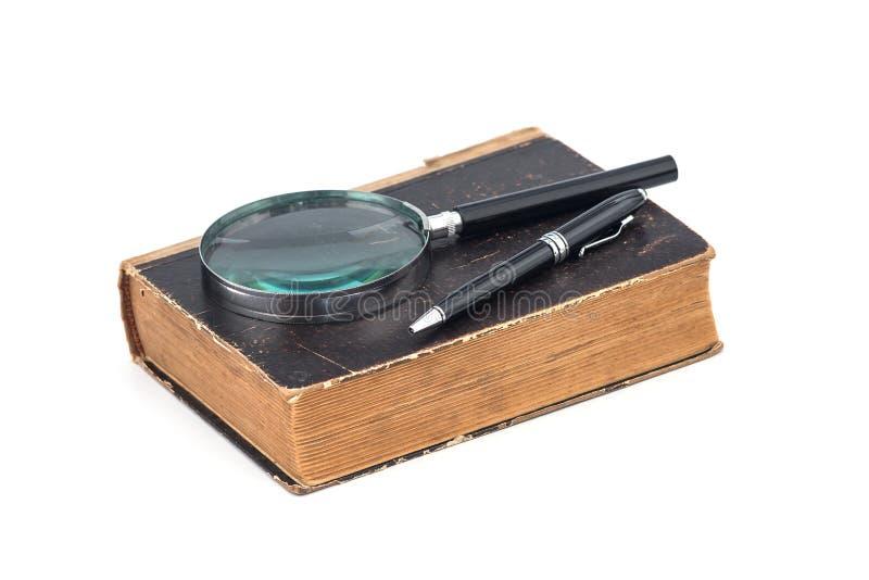 Livro antigo com lente de aumento e caneta sobre fundo branco foto de stock