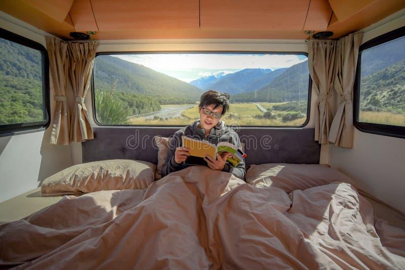Livro asiático novo do compartimento da leitura do homem na camionete de campista imagens de stock royalty free
