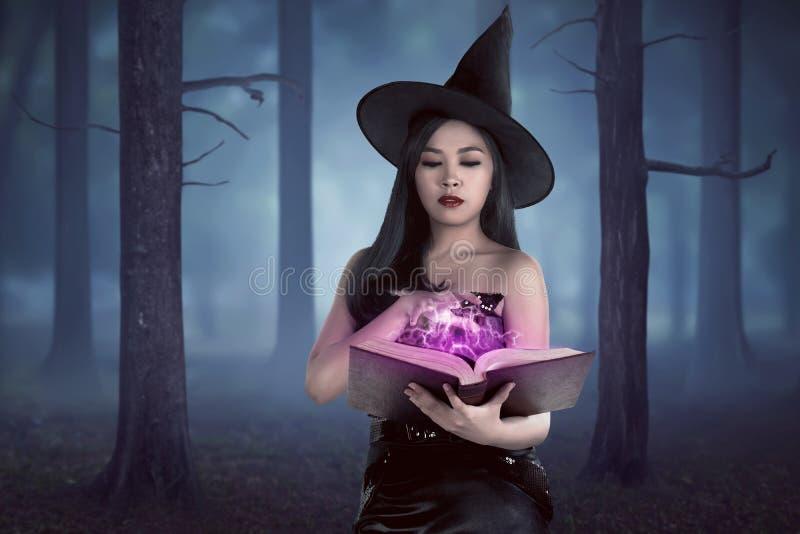 Livro asiático novo do período da terra arrendada da mulher do feiticeiro na floresta com f fotografia de stock royalty free