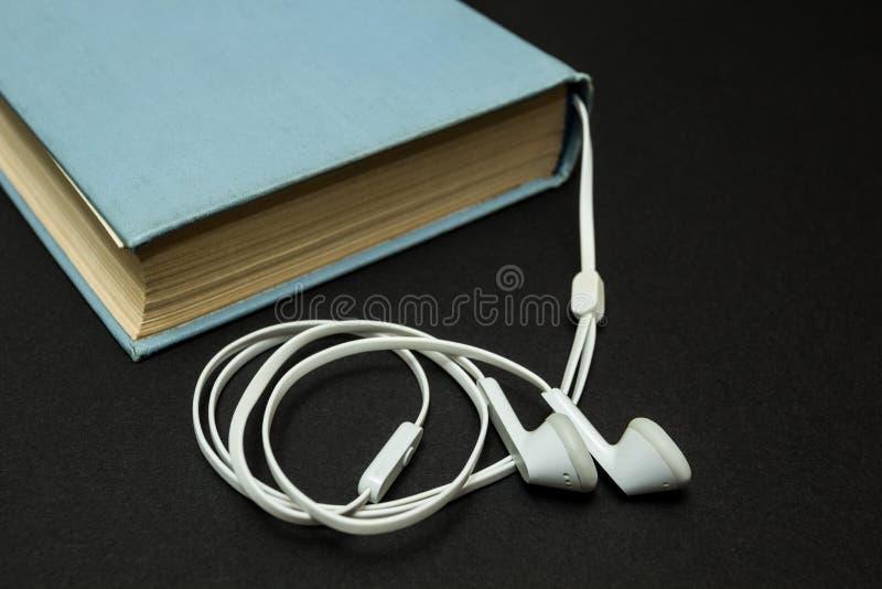 Livro azul velho, e fones de ouvido brancos em um fundo preto fotos de stock royalty free