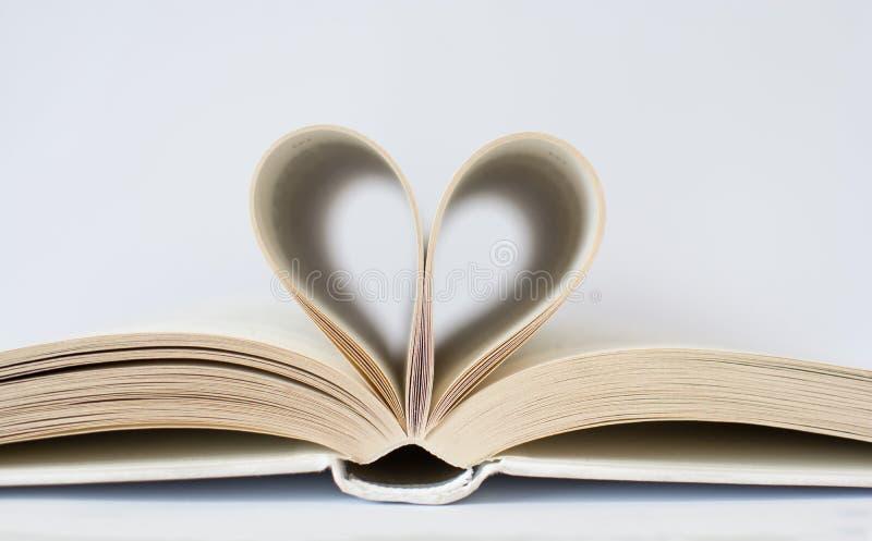 Livro branco com páginas que formam um coração no fundo branco fotografia de stock