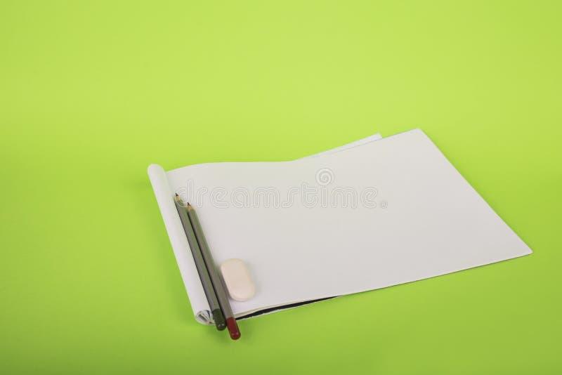 Livro Branco e dois lápis em um fundo verde Álbum para a tiragem e os lápis O artista tira artigos de papelaria em um verde foto de stock