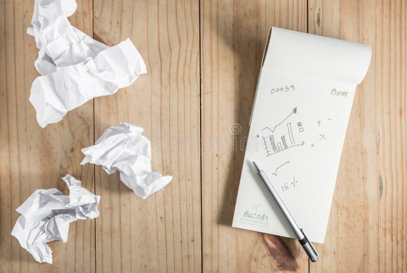 Livro Branco e lápis de papel e cinzento amarrotado no backgro de madeira imagem de stock royalty free