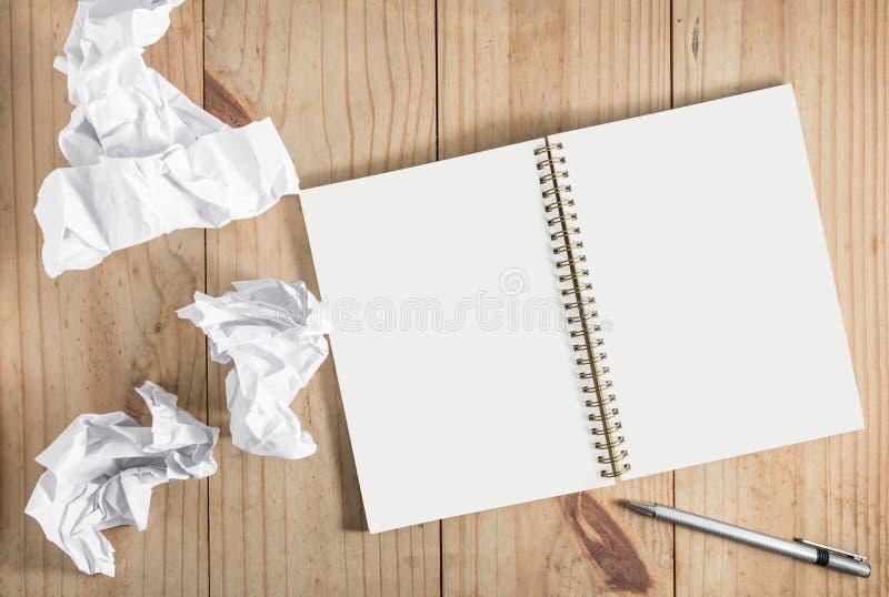 Livro Branco e lápis de papel e cinzento amarrotado no backgro de madeira imagem de stock