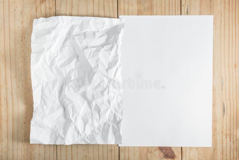 Livro Branco e papel amarrotado no fundo de madeira fotos de stock