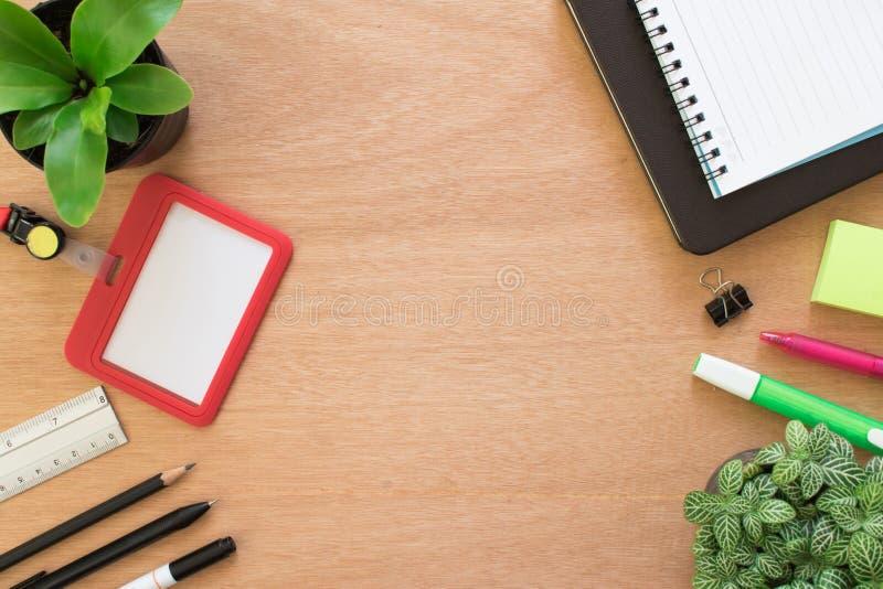Livro, clipe, lápis, régua, destacando a pena, o cartão do empregado, o post-it e o potenciômetro da árvore na mesa de madeira ma fotografia de stock royalty free