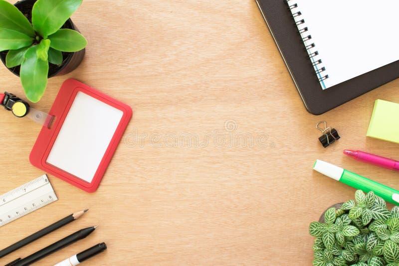 Livro, clipe, lápis, régua, destacando a pena, o cartão do empregado, o post-it e o potenciômetro da árvore na mesa de madeira ma imagens de stock