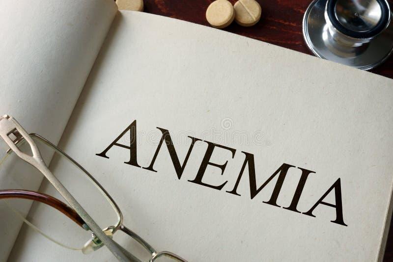 Livro com anemia e comprimidos do diagnóstico imagem de stock