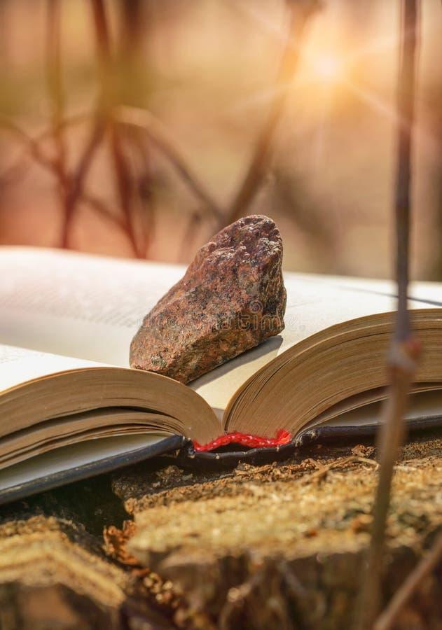 Livro com pedra imagens de stock