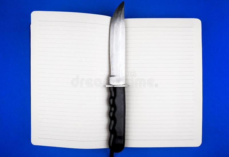 Livro com uma faca fotografia de stock royalty free