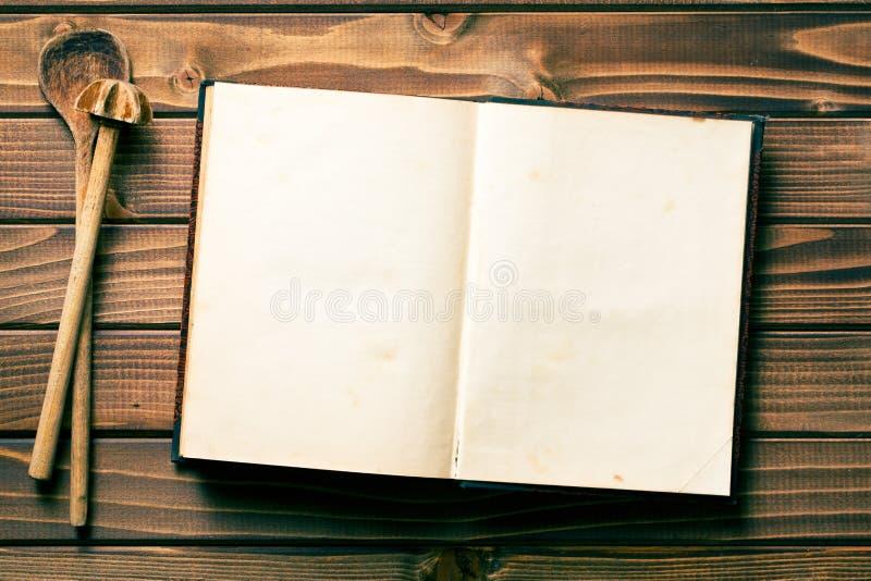 Livro da receita com agitação de colheres foto de stock