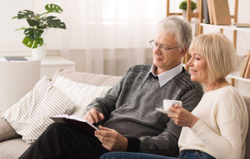 Livro da terra arrendada do homem de pessoa idosa e ilustração mostrar a sua esposa imagens de stock