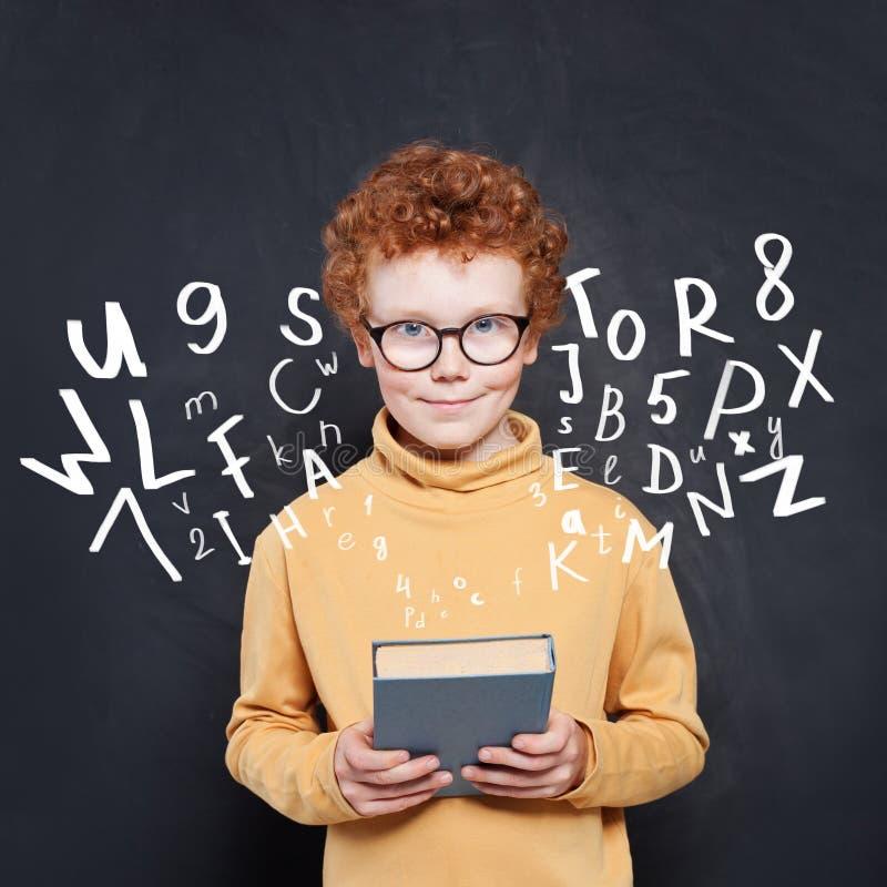 Livro da terra arrendada do menino da criança no fundo do quadro com letras e números fotos de stock royalty free