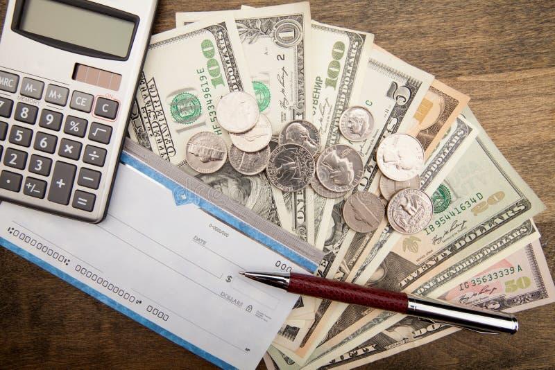 Livro de cheques, pena, calculadora e dinheiro - ascendente próximo fotografia de stock