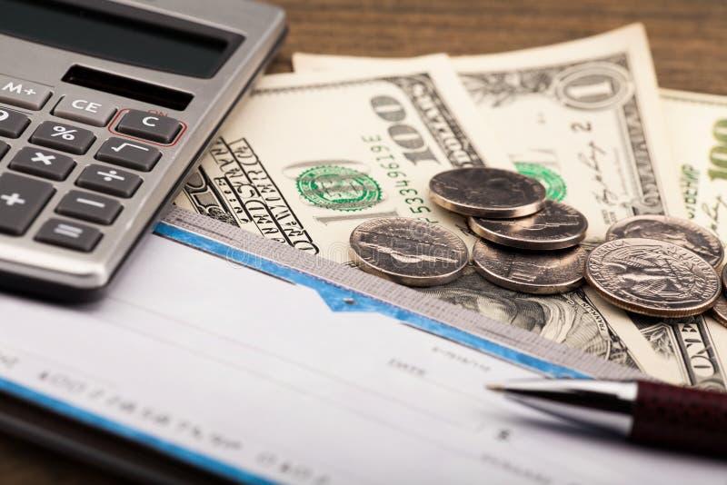 Livro de cheques, pena, calculadora e dinheiro - ascendente próximo imagens de stock