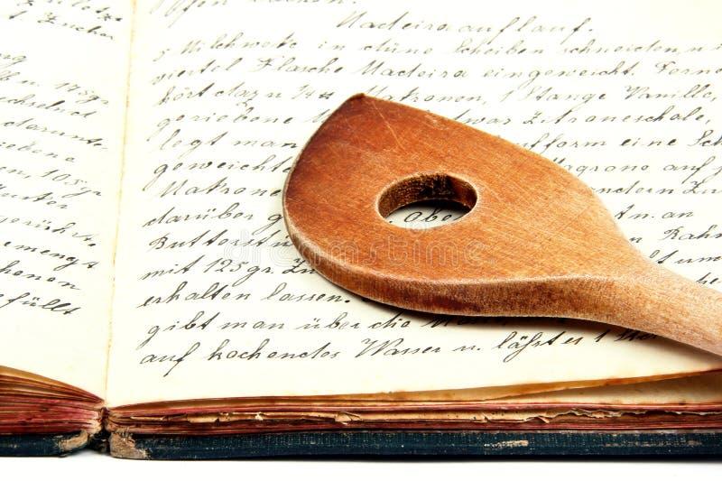 Livro de cozimento velho com colher de madeira imagem de stock royalty free