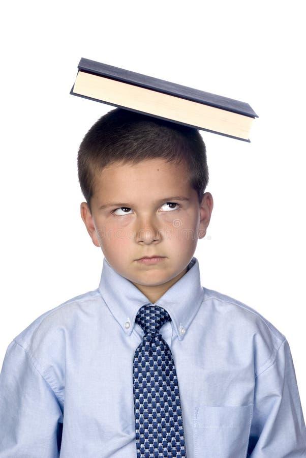 Livro de equilíbrio do menino na cabeça fotografia de stock royalty free