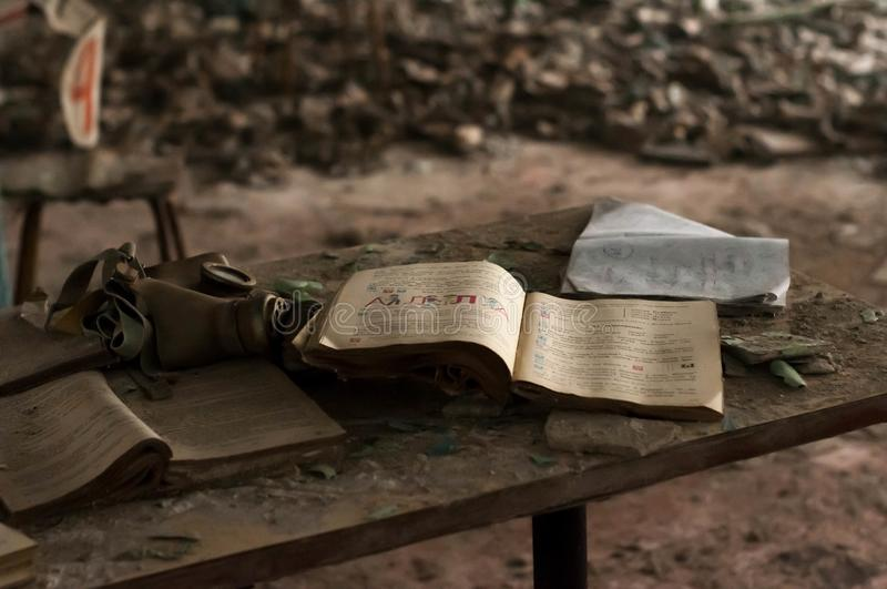 Livro de estudo e máscara de gás abertos na tabela de madeira na frente do rexf com respiradores imagens de stock royalty free