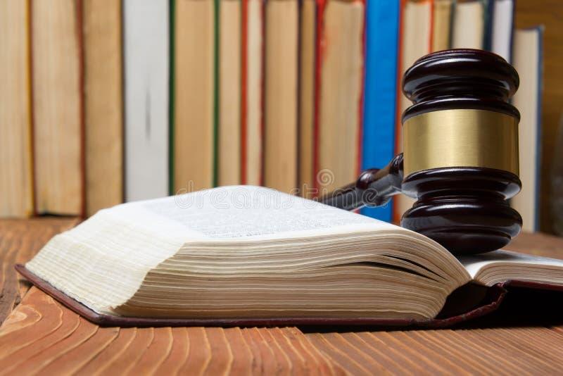 Livro de lei com o martelo de madeira dos juizes na tabela em uma sala do tribunal ou em um escritório da aplicação da lei fotografia de stock