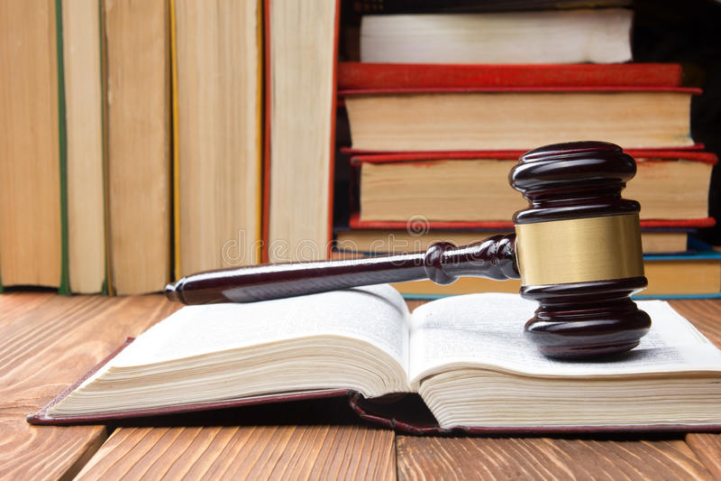 Livro de lei com o martelo de madeira dos juizes na tabela em uma sala do tribunal ou em um escritório da aplicação da lei fotografia de stock royalty free