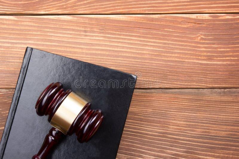 Livro de lei com o martelo de madeira dos juizes na tabela na foto de stock