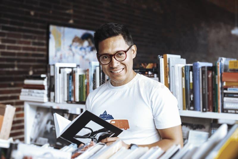 Livro de leitura de óculos novo do homem em umas livrarias imagens de stock