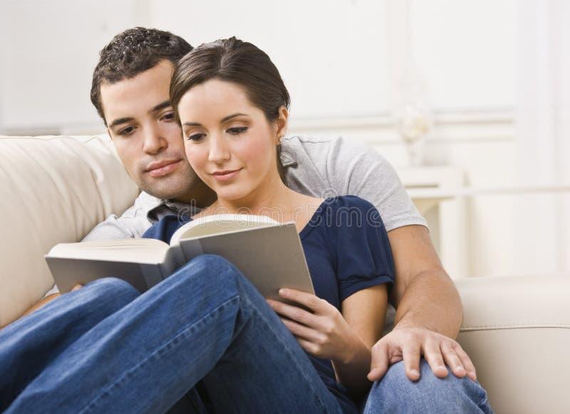 Livro de leitura acolhedor dos pares imagens de stock royalty free