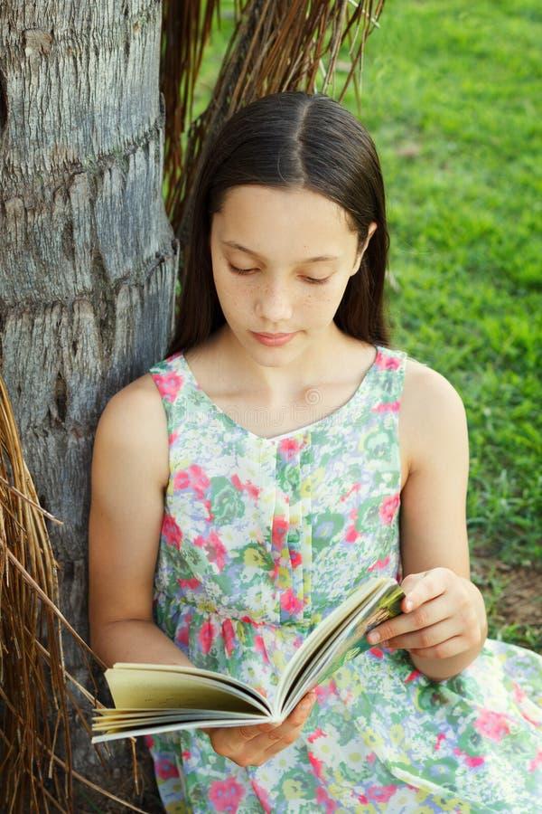 Livro de leitura adolescente bonito da menina que senta-se na grama verde imagem de stock
