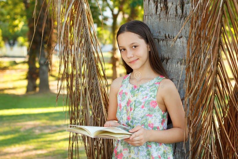 Livro de leitura adolescente de sorriso bonito da menina foto de stock