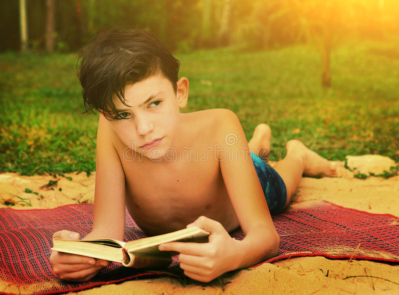 Livro de leitura adolescente do menino na praia fotos de stock
