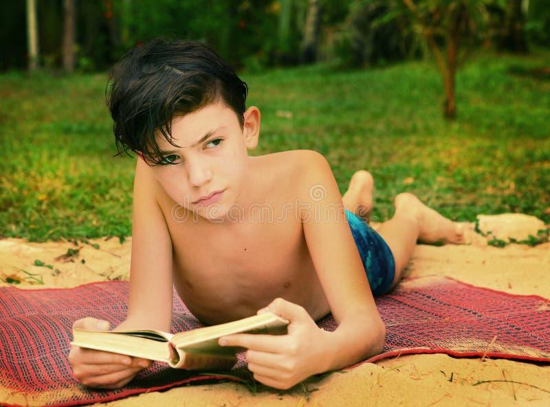 Livro de leitura adolescente do menino na praia fotos de stock royalty free