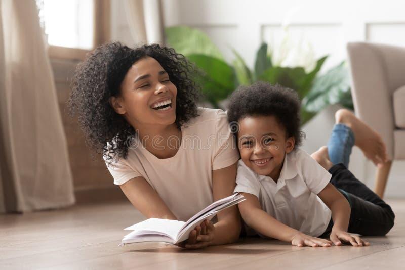 Livro de leitura africano da mamã que ri com filho da criança em casa foto de stock