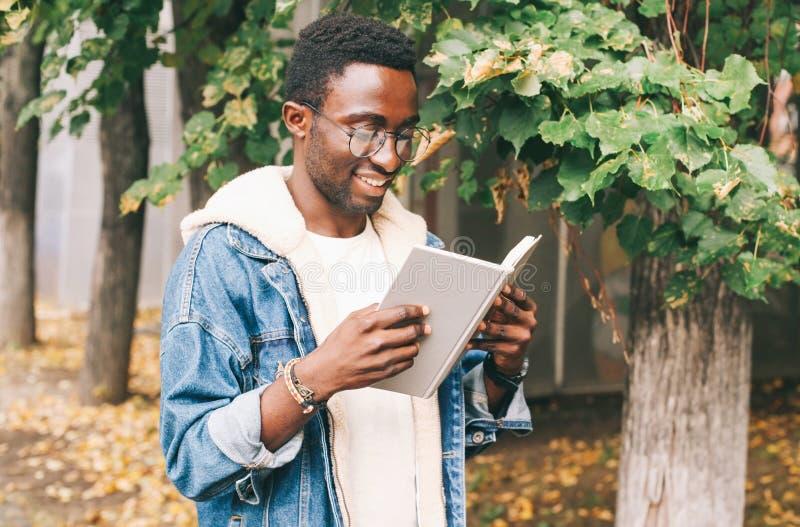 Livro de leitura africano de sorriso feliz do homem do retrato no outono fotografia de stock royalty free