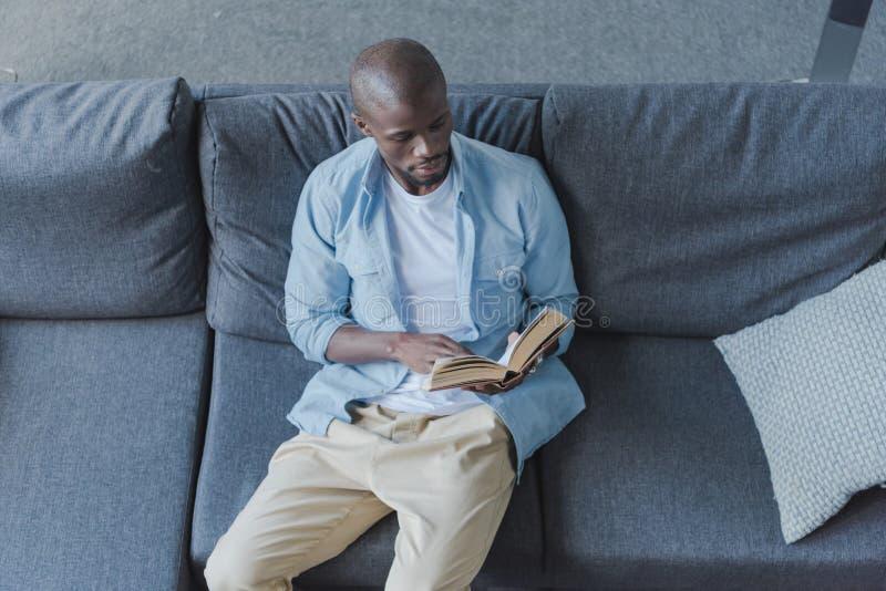 Livro de leitura afro-americano considerável do homem foto de stock royalty free