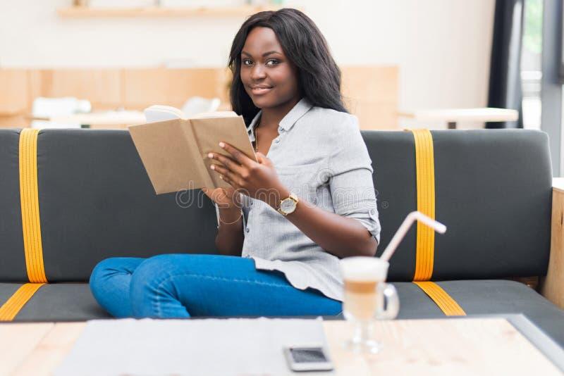 Livro de leitura afro-americano da mulher ao sentar-se no café foto de stock royalty free