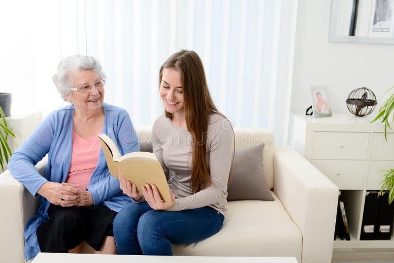 Livro de leitura alegre da jovem mulher para a mulher superior idosa em casa imagens de stock royalty free