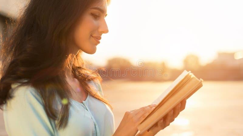 Livro de leitura ao ar livre Jovem mulher que anda na cidade no por do sol foto de stock royalty free