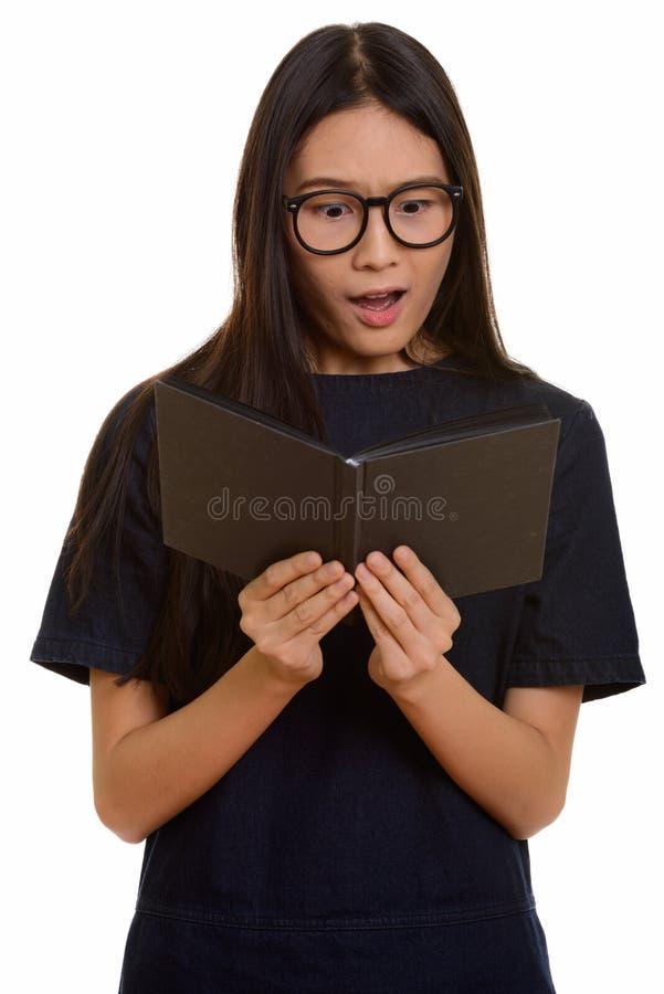 Livro de leitura asiático bonito novo do adolescente ao olhar sh foto de stock royalty free