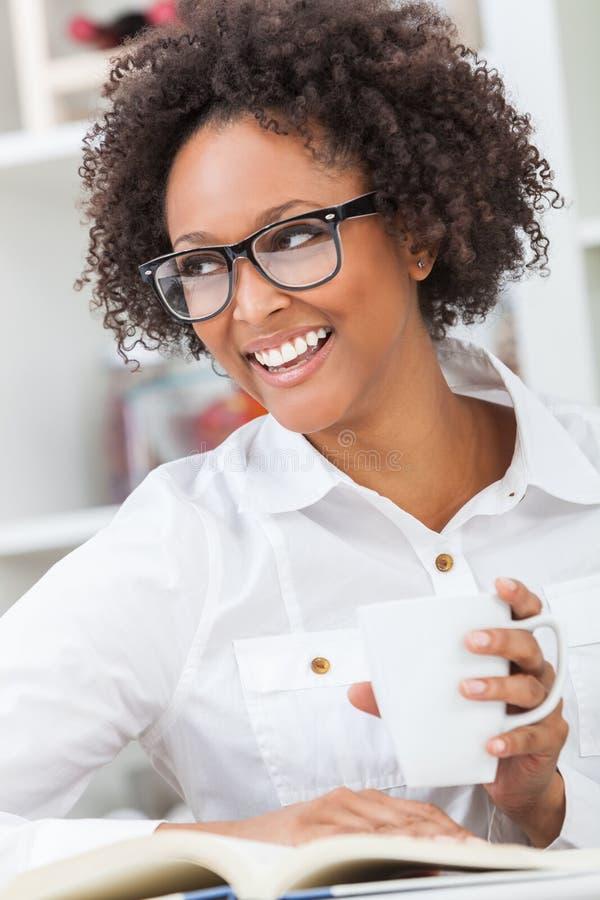Livro de leitura bebendo do café da menina afro-americano da raça misturada foto de stock royalty free