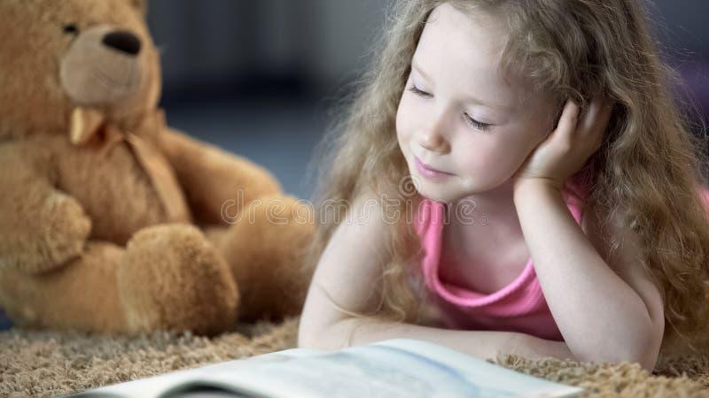 Livro de leitura bonito concentrado da menina, encontrando-se no tapete, educação pré-escolar fotografia de stock