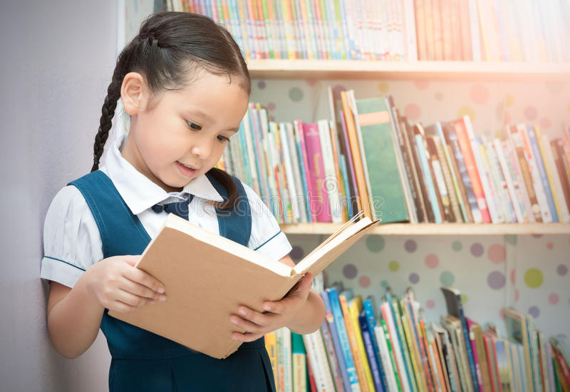 Livro de leitura bonito da menina do estudante asiático na biblioteca fotografia de stock